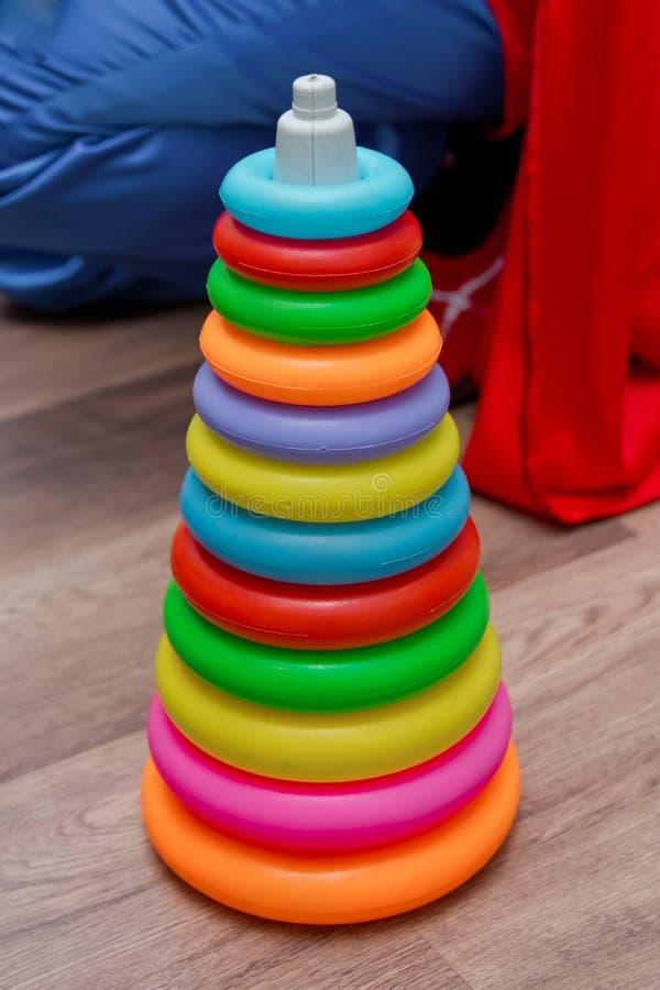 Pirâmide plástica colorida do brinquedo do arco-íris para crianças no fundo azul Os brinquedos multi-coloridos brilhantes das cri fotos de stock royalty free