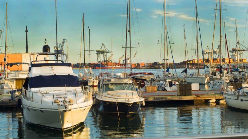 Pir med förtöjde yachter och segelbåtar på bakgrunden av skeppsdockorna och behållare av stadsporten i det gula solnedgångljuset, arkivbilder