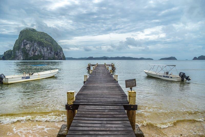 Pir med fartyg på bakgrunden av ett tropiskt hav och steniga berg i den molniga dagen, El Nido, Palawan, Filippinerna Augusti 201 arkivbilder