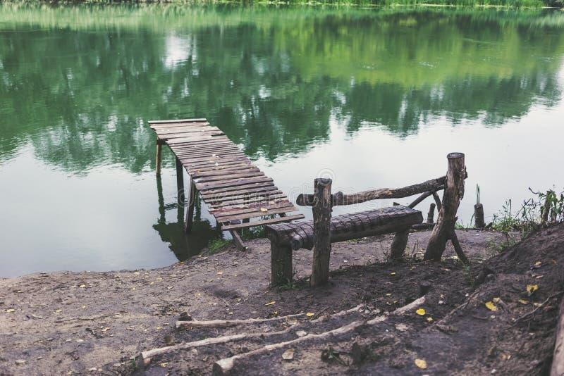 Pir på en lugna flod i sommaren Träpirbro arkivbild