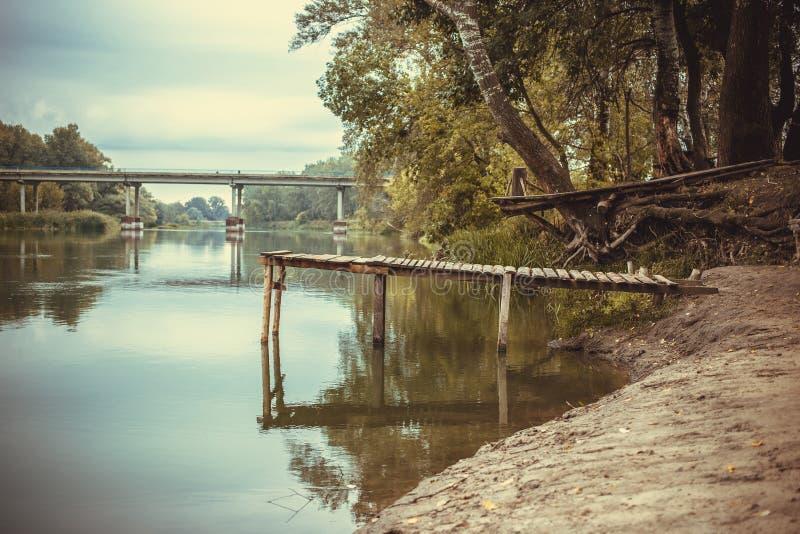 Pir på en lugna flod i sommaren Träpirbro arkivfoto