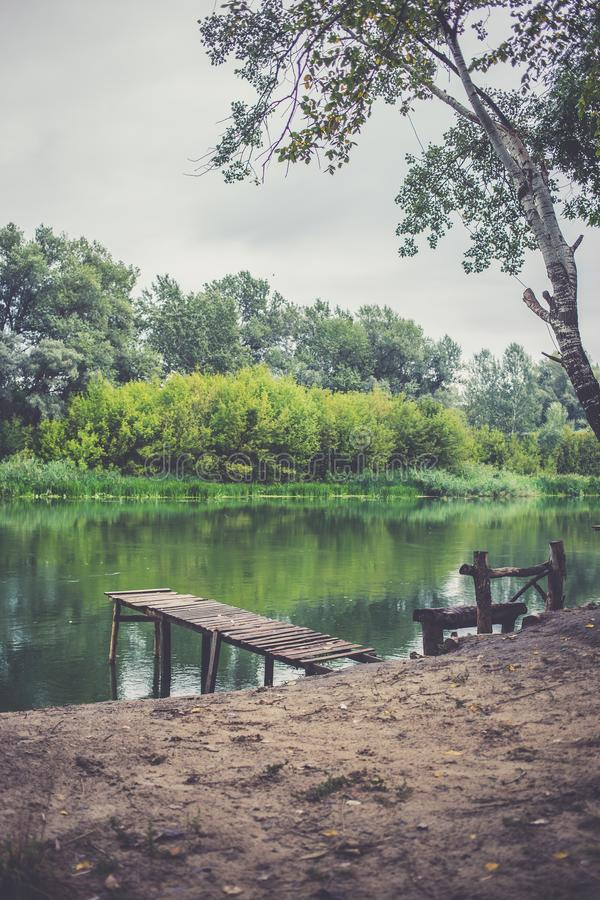 Pir på en lugna flod i sommaren Träpirbro royaltyfri bild