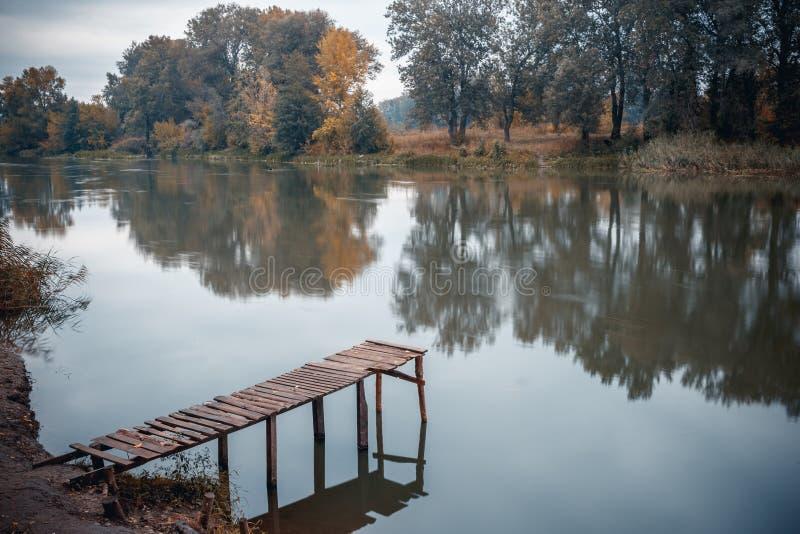 Pir på en lugna flod i sommaren Träpirbro arkivfoton