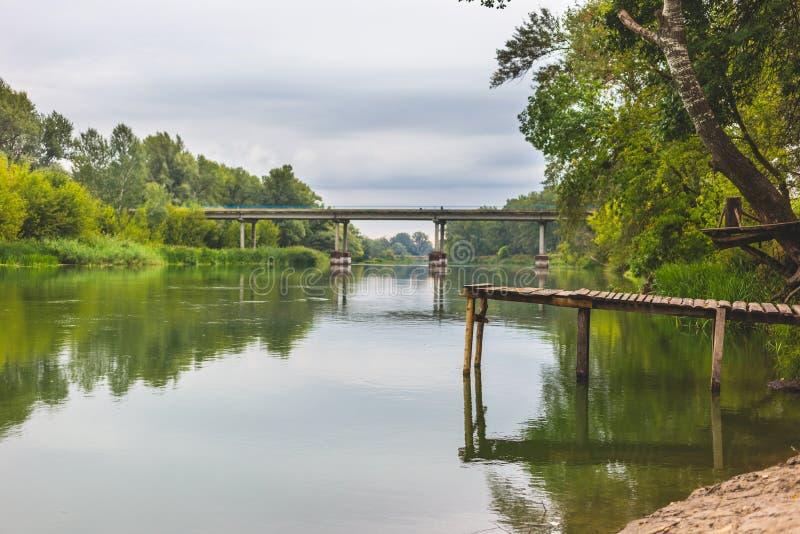 Pir på en lugna flod i sommaren Träpirbro royaltyfria foton