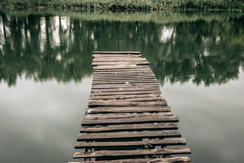 Pir på en lugna flod i sommaren Träpirbro fotografering för bildbyråer