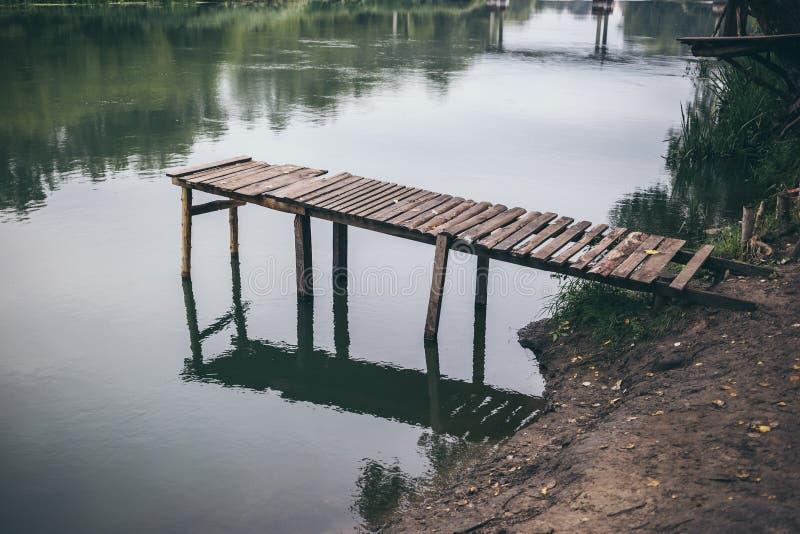 Pir på en lugna flod i sommaren Träpirbro royaltyfri fotografi