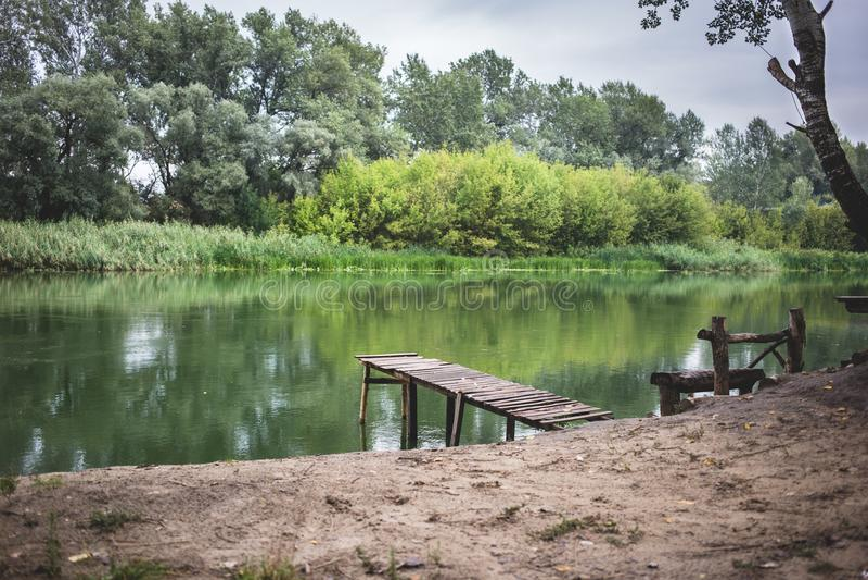 Pir på en lugna flod i sommaren Träpirbro royaltyfri foto