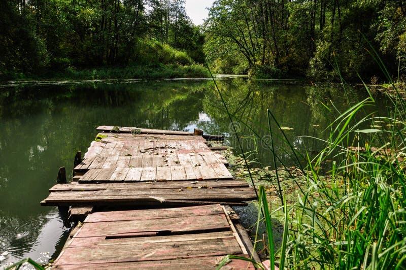 Pir på en lugna flod i sommaren Träpirbro i morgonen Ställe för att fiska i floden arkivbild