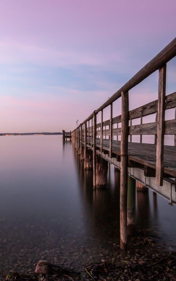 Pir på en sjö på solnedgången arkivbild