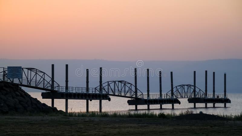 Pir som sticker ut ut in i havet av Galilee på soluppgång royaltyfri foto