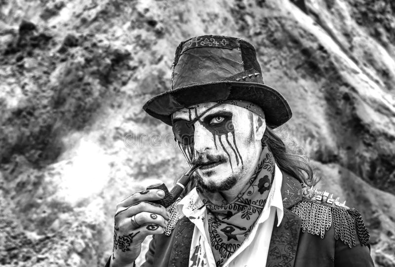 Piraatschurk van de middenleeftijden om zwart-witte pijp te roken, stock afbeeldingen