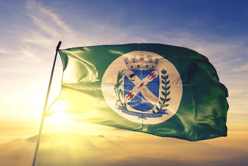 Piracicaba du drapeau brésilien agitant sur le brouillard du lever du soleil images stock
