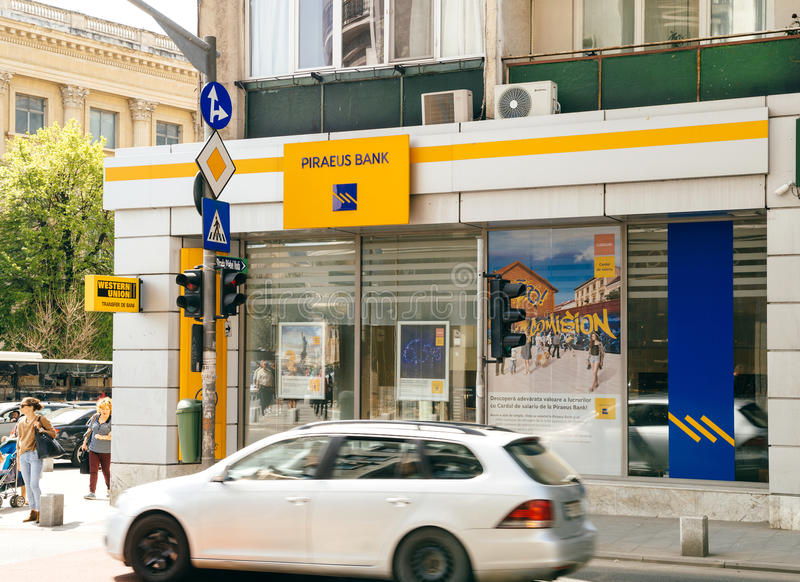 Piraeus Bank agency facade with customers walking in front and c. BUCHAREST, ROMANIA - APR 1, 2016: Piraeus Bank agency facade with customers walking in front royalty free stock photo