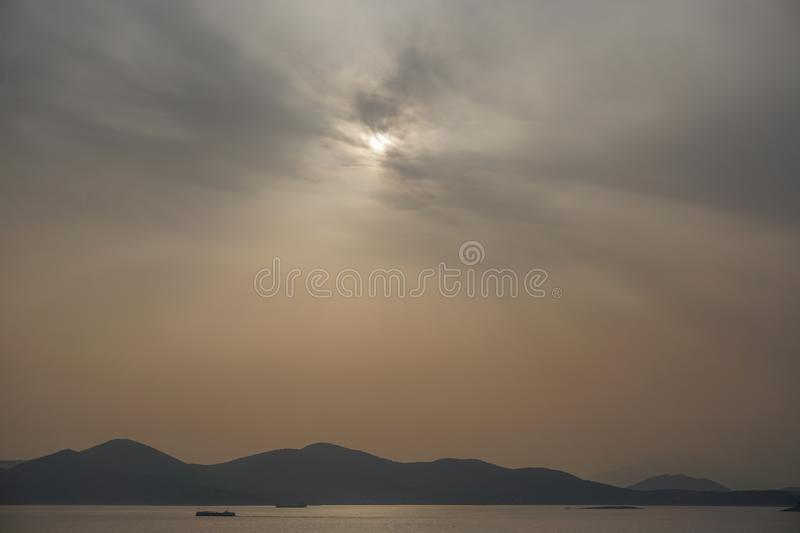 Piraeus, Greece: Sunset on the Saronic Gulf. Piraeus, Greece: Sunset over islands in the Saronic Gulf Gulf of Aegina reveals a large amount of dust pollution in stock images