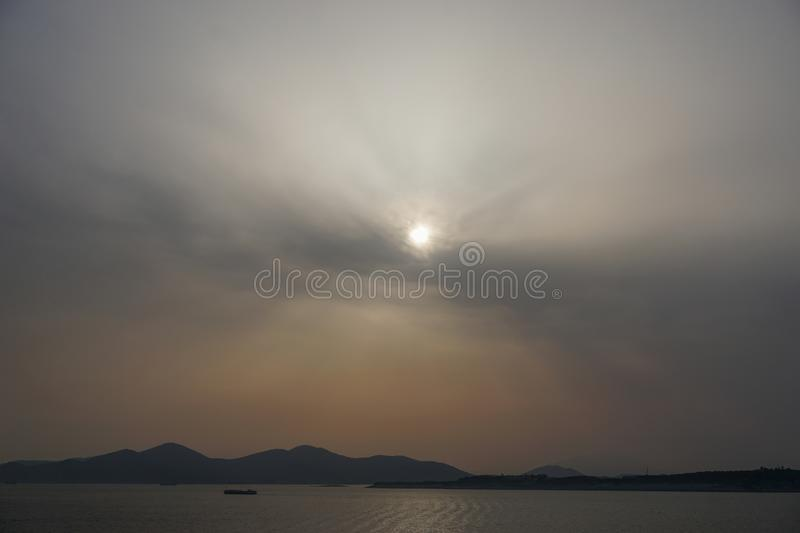 Piraeus, Greece: Sunset on the Saronic Gulf. Piraeus, Greece: Sunset over islands in the Saronic Gulf Gulf of Aegina reveals a large amount of dust pollution in stock photo