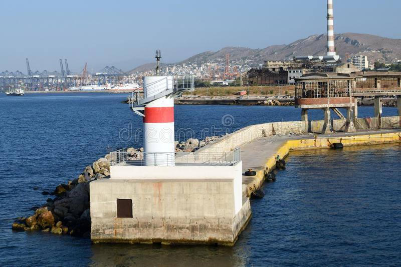Piraeus lighthouse with a red stripe to navigate ships that enter the port of Athens. The view from the outgoing ship, the path from the lighthouse to the stock photography