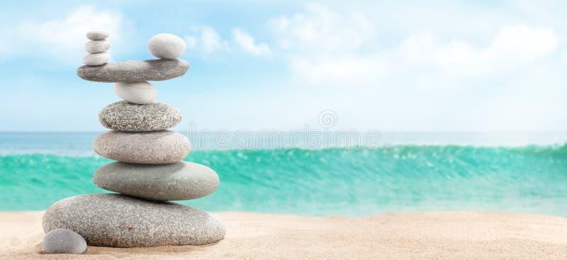 Piramida kamyków morskich na plaży z piaskiem słonecznym obrazy royalty free