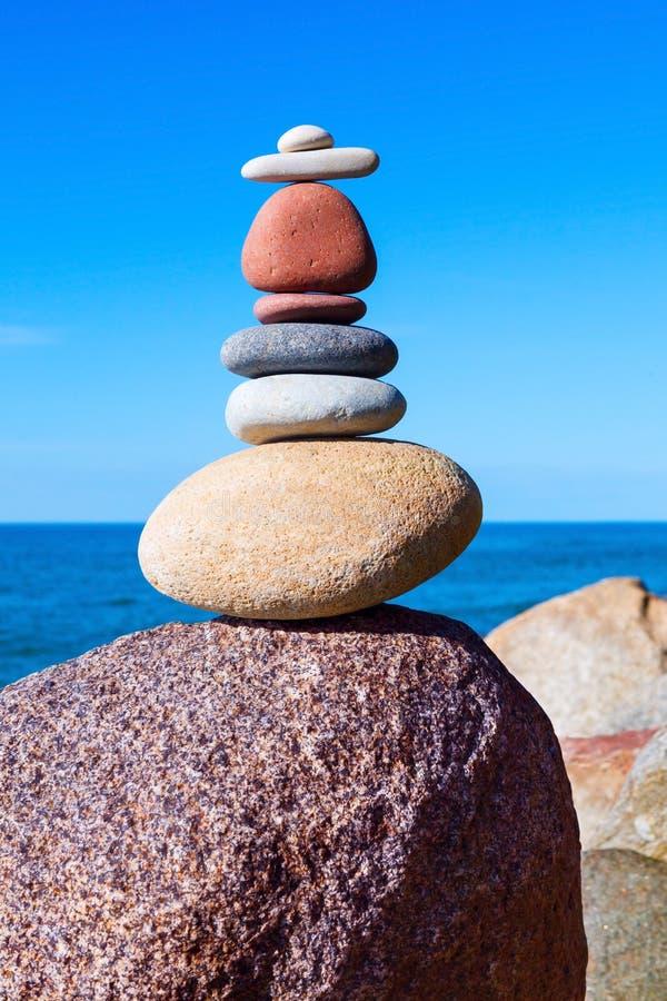 Piramide dalle pietre colorate su un fondo del mare Concetto dell'equilibrio fotografia stock libera da diritti