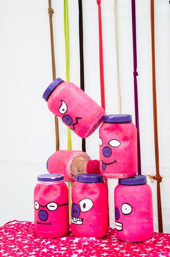 Piramide dei recipienti di plastica con i fronti divertenti per gettare le palle su un fondo a strisce fotografie stock libere da diritti