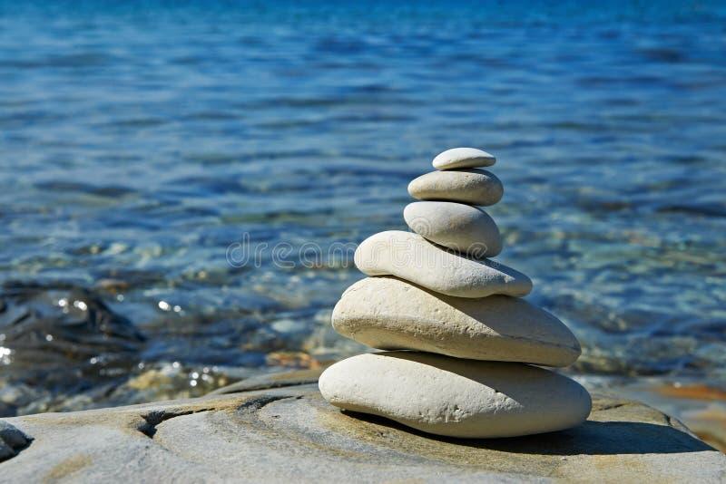 Piramide dell'equilibrio di zen delle pietre nella riva di mare fotografia stock