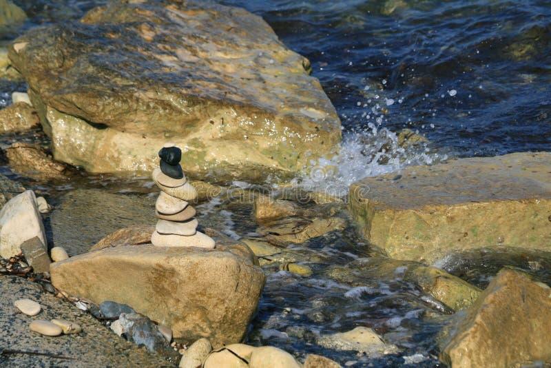 Piramide della pietra di zen sulla roccia del mare fotografia stock libera da diritti