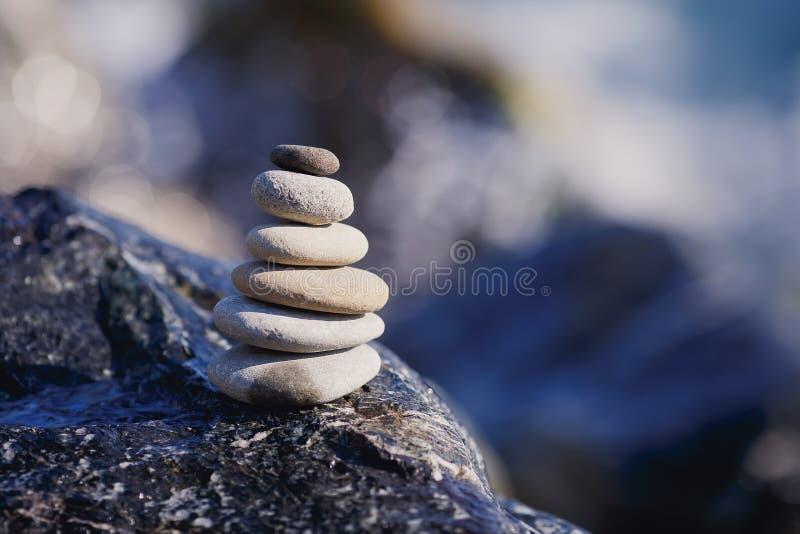 Piramide di pietra equilibrata sulla riva di acqua blu La stazione termale lapida la scena del trattamento, zen come i concetti T fotografie stock