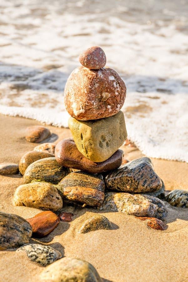 Piramide di pietra di zen ad una spiaggia con spuma fotografie stock