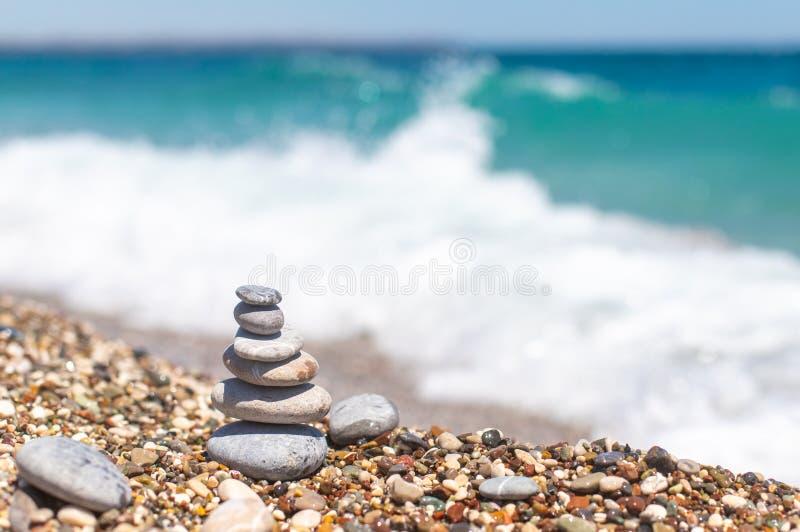 Piramide di pietre vicino all'oceano Obo da ciottoli Torre di pietra sulla spiaggia, onde blu dietro Equilibrio, tranquillità men immagini stock