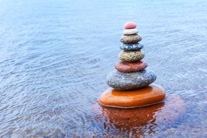 Piramide di zen della roccia dei ciottoli variopinti che stanno nell'acqua immagini stock