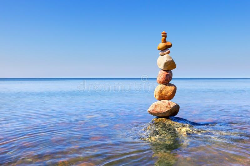 Piramide di zen della roccia dei ciottoli variopinti che stanno nell'acqua sui precedenti del mare immagine stock