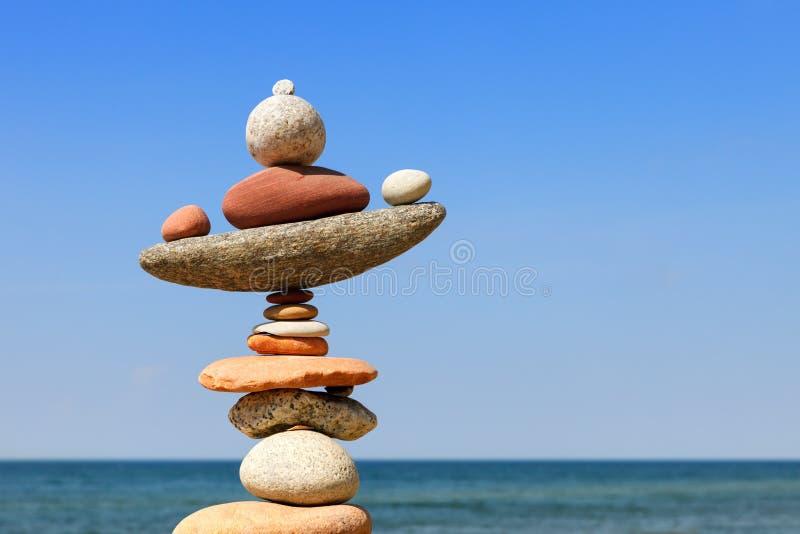 Piramide di zen della roccia dei ciottoli variopinti su una spiaggia sui precedenti del mare fotografia stock libera da diritti