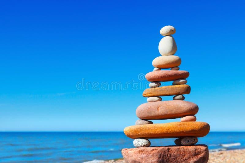 Piramide di zen della roccia dei ciottoli variopinti su una spiaggia sui precedenti del mare Concetto di equilibrio, di armonia e fotografia stock
