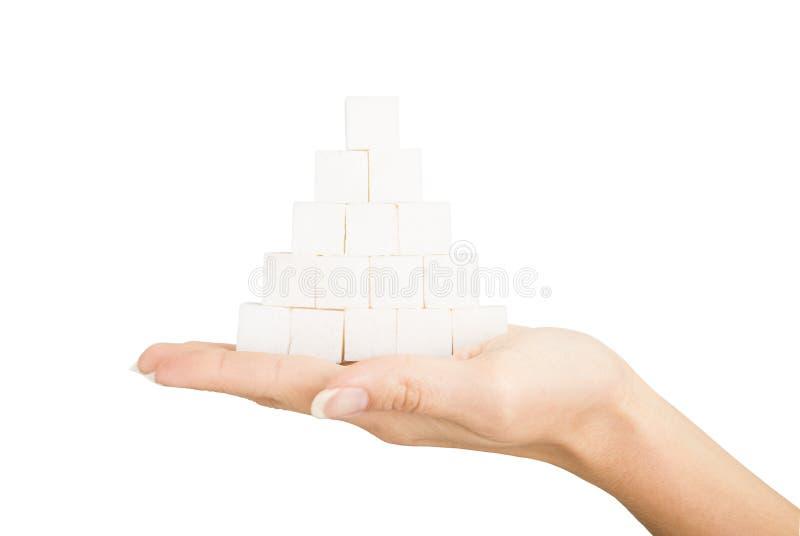 Piramide di zucchero grumoso nella palma su fondo bianco immagini stock