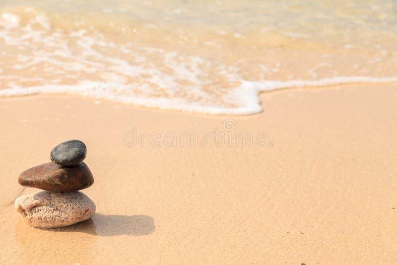 Piramide van de stenen op het zandige strand bij oceaanachtergrond royalty-vrije stock afbeeldingen