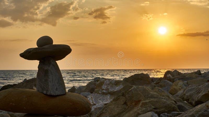 Piramide van de stenen op zonsondergang, kustachtergrond worden geïsoleerd die royalty-vrije stock foto's