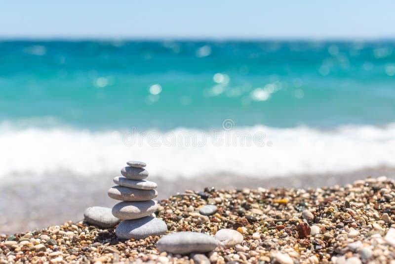 Piramide van stenen ERST-bulkgoed-aardolie van kiezelstenen Steentoren op het strand tegen het blauwe overzees Het saldo, vrede v stock foto's
