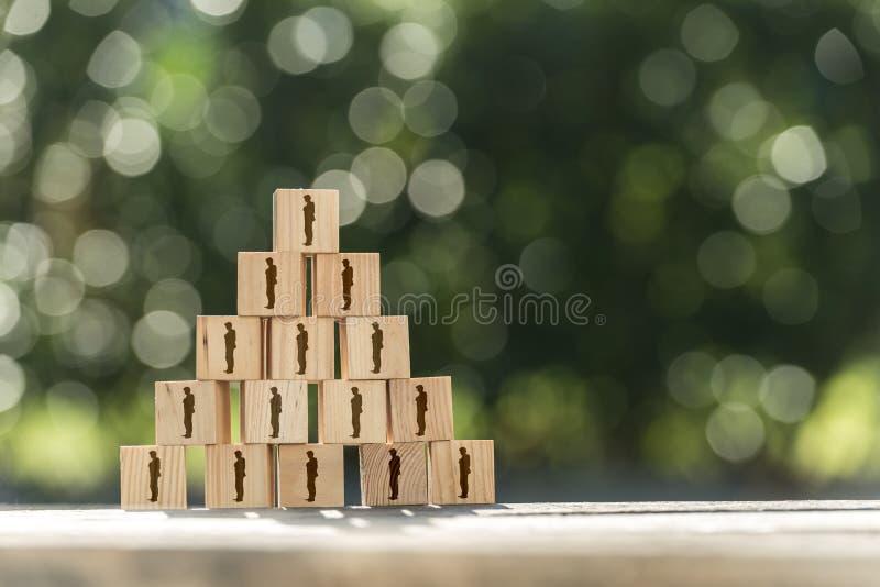 Piramide van stuk speelgoed houten blokken met menselijke pictogrammen stock afbeeldingen