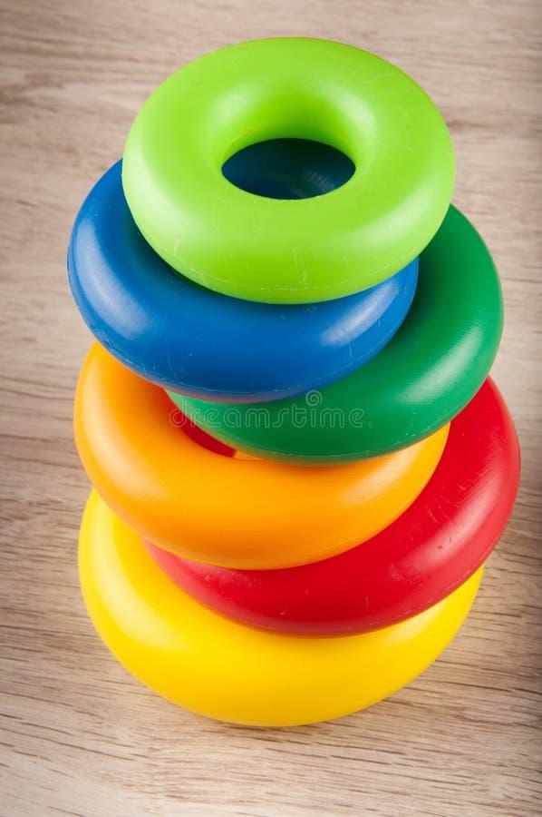 Piramide van stuk speelgoed plastic kleurrijke ringen op lijst stock foto