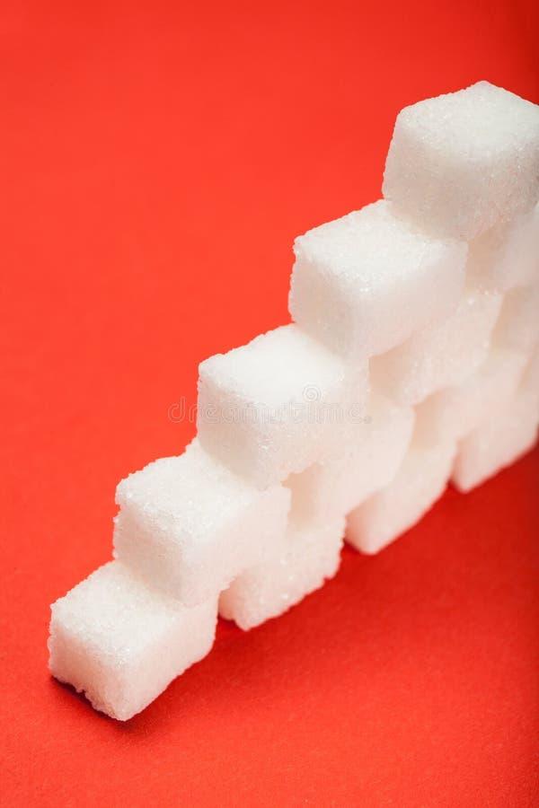 Piramide van suikerkubussen, die op een rode achtergrond wordt geïsoleerd verticaal stock foto