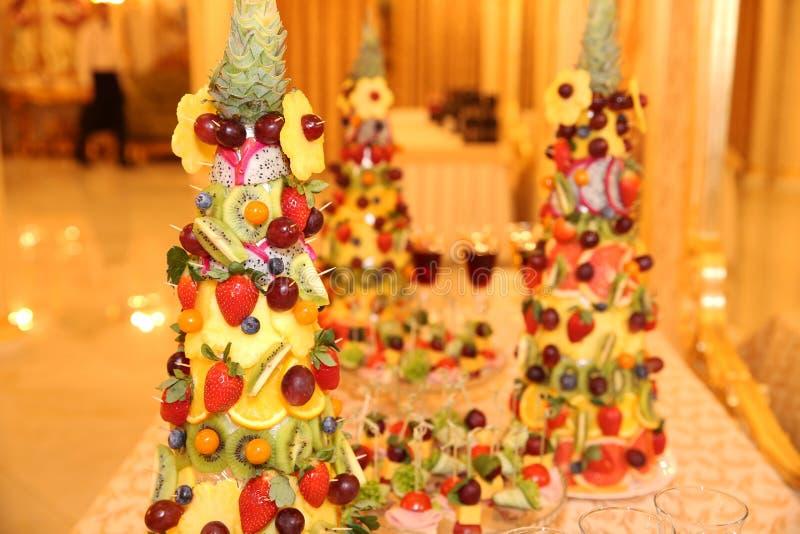 Piramide van verse vruchten en bessen op een lijst met rode wijn en champagne royalty-vrije stock foto's