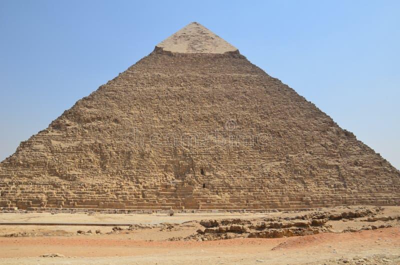 Piramide in zandstof onder grijze wolken stock foto