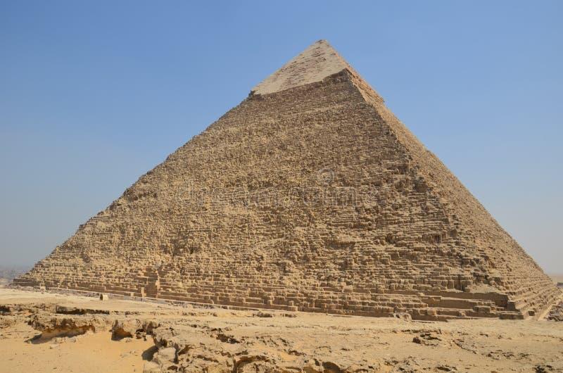 Piramide in zandstof onder grijze wolken stock afbeeldingen