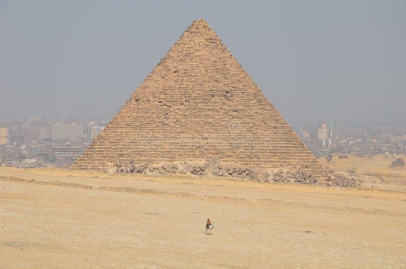 Piramide in zandstof onder grijze wolken stock fotografie