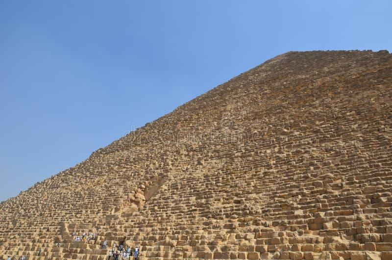 Piramide in zandstof onder grijze wolken stock afbeelding