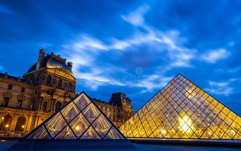 Piramidi del Louvre con cielo blu crepuscolare nuvoloso immagine stock