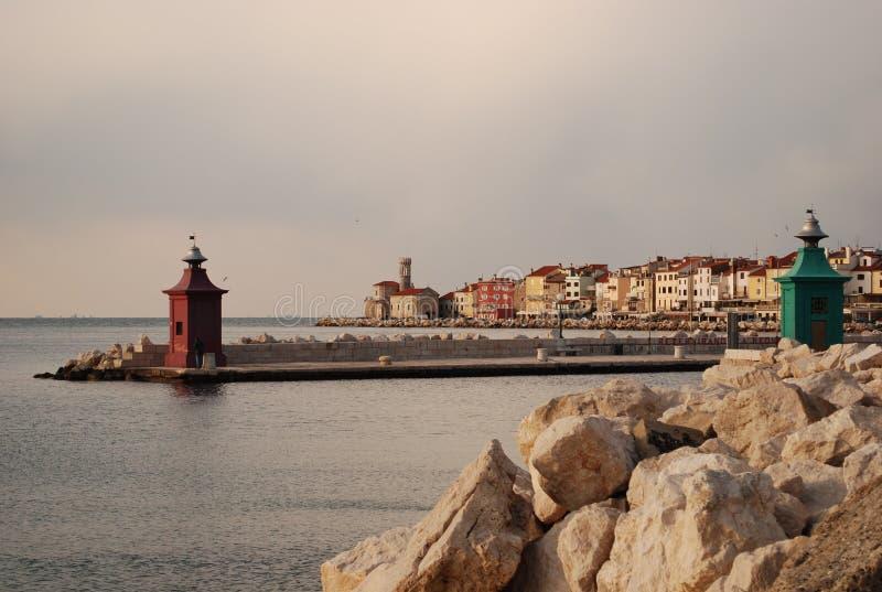 Piran la ciudad de los dos pequeños faros uno verdes y de un rojo que pasa por alto el mar adriático fotografía de archivo libre de regalías