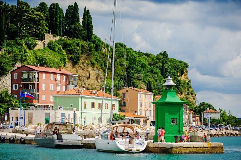 PIRAN, SLOVENIË - 18 JULI 2013: stad en havenmening in de zomerdag bij groene vuurtoren stock foto's