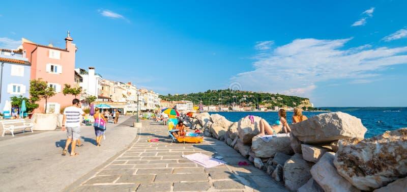 PIRAN, SLOVENIË - 24 7 2018: Pirankust en strand op Adriatische overzees De toerist zwemt in overzees of loopt op stadsstraat De  royalty-vrije stock afbeelding