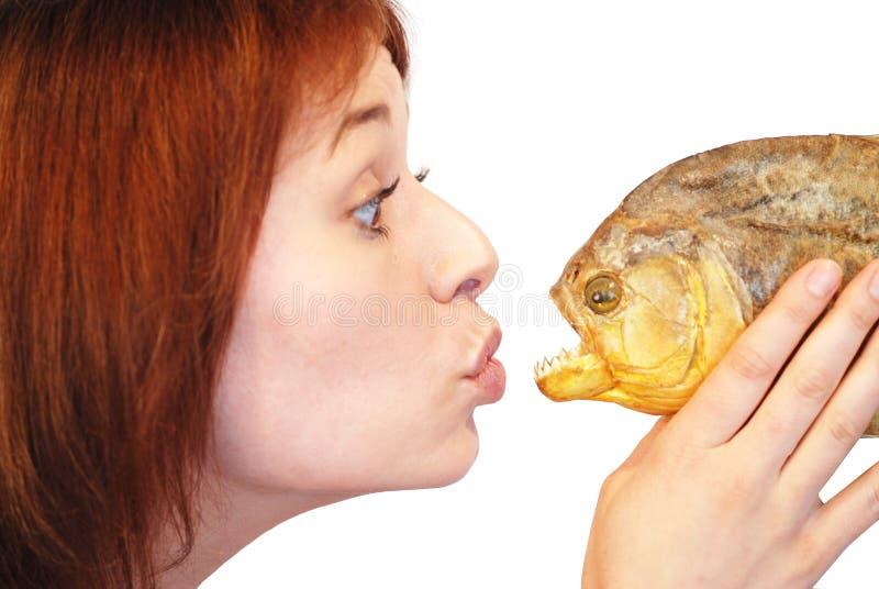 Piranha. Shot of girl kissing piranha, isolated on white background stock photography