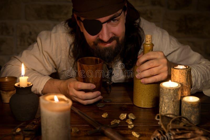 Pirat mit Rum und Lose Kerzen und goldnuggets, Konzept m lizenzfreie stockfotografie